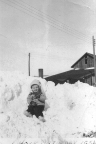 Easter weekend, 1951: The first granddaughter of Earl and Fern Moyna, Don & Madelyn (Moyna) Hosek's little girl, 3-year-old Chris helps her grandfather Earl dig the barn and shop out of a freakish late winter blizzard on Good Friday. Nearly two feet of snow fell in less than 12 hours over night. The buried shop and barn are obscured by the drifts and the bank plowed up by Village employee, Ed Berryhill.