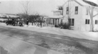 """Winter of 1945: My Sister Earlene in front of Earl's 1941 Chevy. A good view of the house at 826 Frankfort Ave. Tourists often stopped to ask about the """"unusual roof."""" Not obvious in this photo was that the gable ends of the roof were cut off or """"hipped"""" by a Swiss carpenter named John Weiss whom Earl hired to re-roof the place while Pa and Ma visited his mother in Detroit. Pa asked him why he did that and John said, """"So it would look right."""" He explained that all the houses where he came from in the Alps were built like that, to reduce snow and ice damage in winter. Ma was furious until tourists started stopping to comment on how unique and stylish it looked. Margaret Davidhizar, who lives there now, painted it black and had the gable ends restored."""